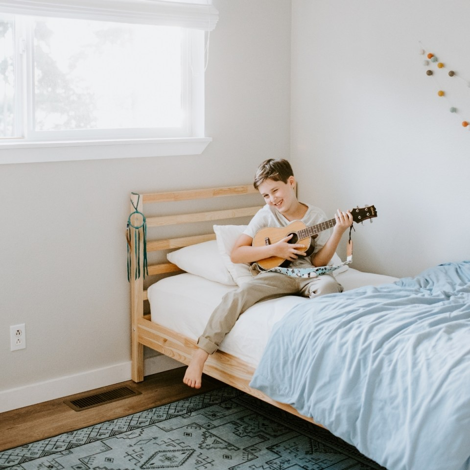 Homeschooling boy playing the ukulele on his bed in his minimalist kids bedroom while winking.