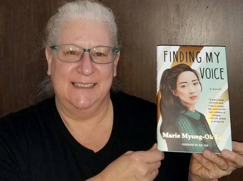 """Melanie Hooper, 57, of Hibbing, holds up a copy of the newest edition of """"Finding My Voice."""""""