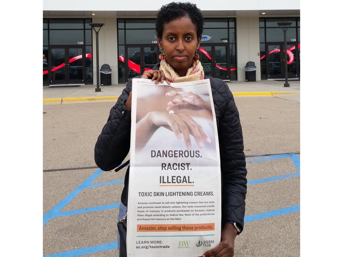 "Image of Amira Adawe standing outside and holding a poster that reads ""Dangerous. Racist. Illegal. Toxic skin lightening creams."""