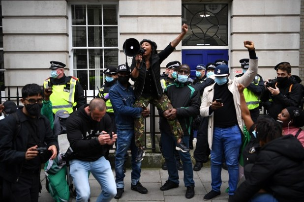 Protestors shout slogans as they raise their fists during a protest action against police brutality in Nigeria, in New Cavendish Street in central London on October 24, 2020.