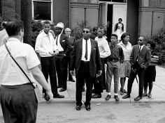 Members of the First Baptist Church and demonstrators, including pastor Rev. Kelly Miller Smith, center, look on as two of their members get arrested on charges of brick throwing that broke a car windshield May 11, 1963. Harold Lowe Jr. / The Tennessean