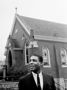 The Rev. Kelly Miller Smith, pastor of First Baptist Church, discusses plans April 4, 1964 for building a new structure at the present church site, 319 Eighth Ave., N. Behind him is the historic, 69-year-old church building that will be razed when the new one is constructed. Jack Corn / The Tennessean