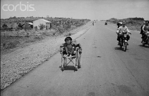 14 Apr 1975, Near Houng Loc, South Vietnam --- Houng Loc, South Vietnam: Crippled boy pushes his wheelchair along Highway One, April 14, 1975, near Houng Loc, 28 miles north of Saigon. Refugees flee down this road daily hoping to reach safety in Saigon. --- Image by © Bettmann/CORBIS