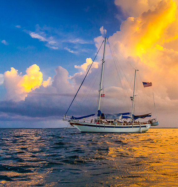 Traditional sailboat anchored during a dramatic golden and blue sunset in Abaco Bahamas. The sailing Ketch Colony II off Powell Cay