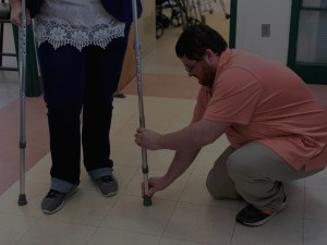 Man helping somebody with the height of their crutches