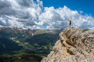 hiker atop a mountain peak with arms raised