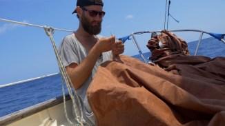 Der Captain näht das Unterliek der Genua