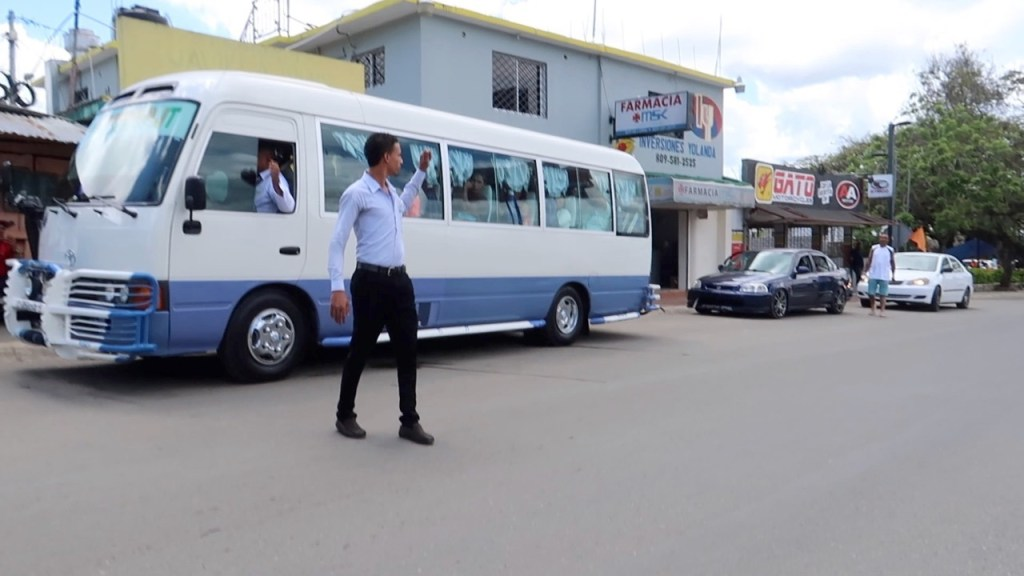 Picture of man directing people into a bus