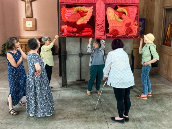 The daughters of Margaret Hays, along with Joann Bailey, Sherry Garman, and Sandy Piscetello inspect the condition of the banner, July 2021.