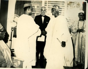 Chief Obafemi Awolowo shaking hands with Oba Oyekan II & Sir Kofo Abayomi seated