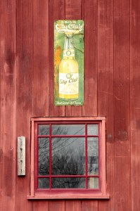 A second story window and an old City Club Beer sign above it at 159 Banfil.
