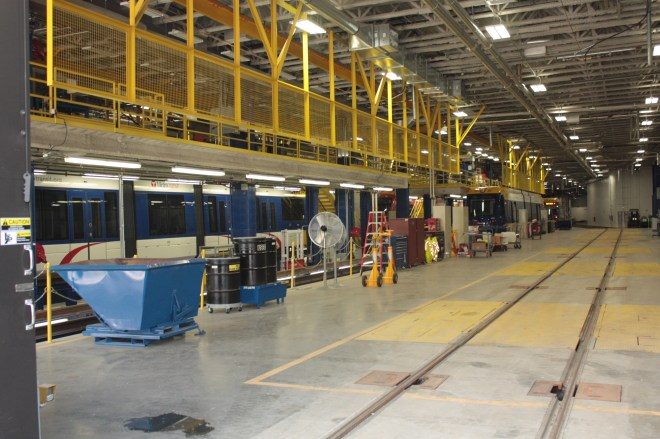 This is where the real work is done. The catwalk with the yellow fencing allows mechanics to work on the upper parts of light rail cars.