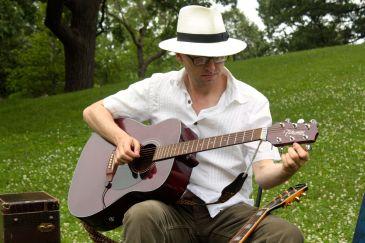 Artistic Director Joseph Papke tunes his guitar as show time grows near.
