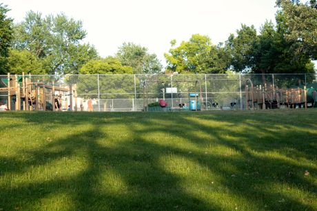 The playground bookends two tennis courts.  Shadows from the trees create an unusual pattern on the grass.