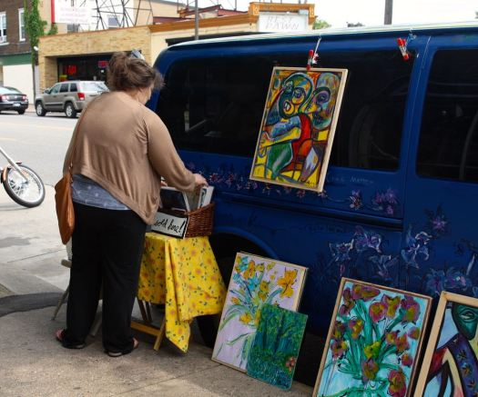 A passerby looks through Gretchen's art along West 7th Street.