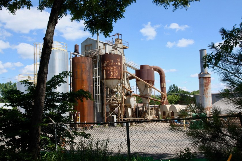 The City's asphalt plant as seen from Richard's back yard. The cyclone fence separates Kevin's property from that of the asphalt plant.