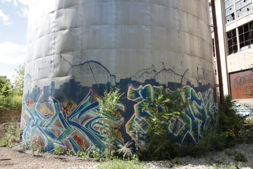 A storage tank next to the steam plant wears an elaborately spray painted design.