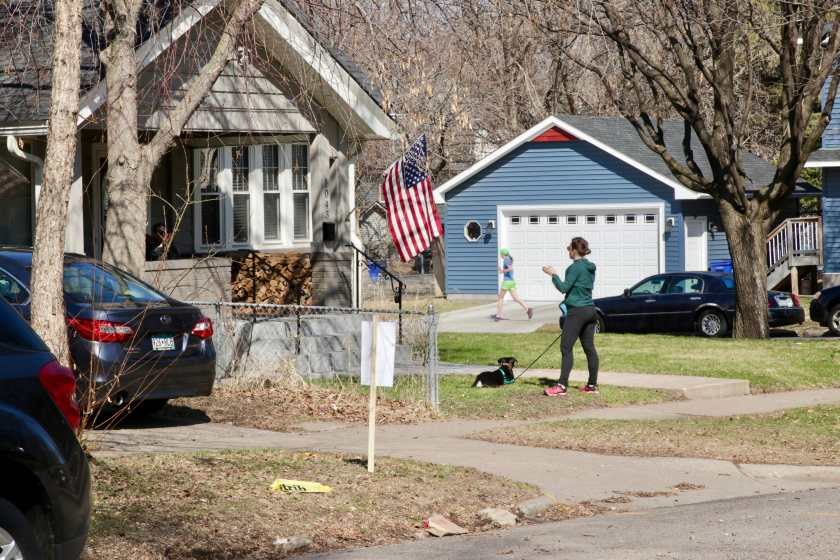 Two neighbors chat – from a distance – at 1043 Dayton, while a solitary jogger passes by across the street.