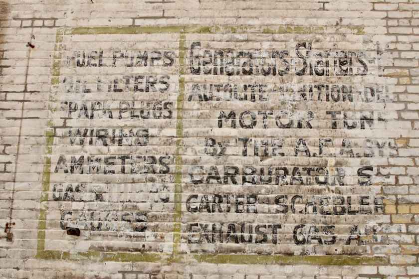 Perhaps the sign, faded by time and the elements on the east wall offers a clue to a previous use of the back part of the building?