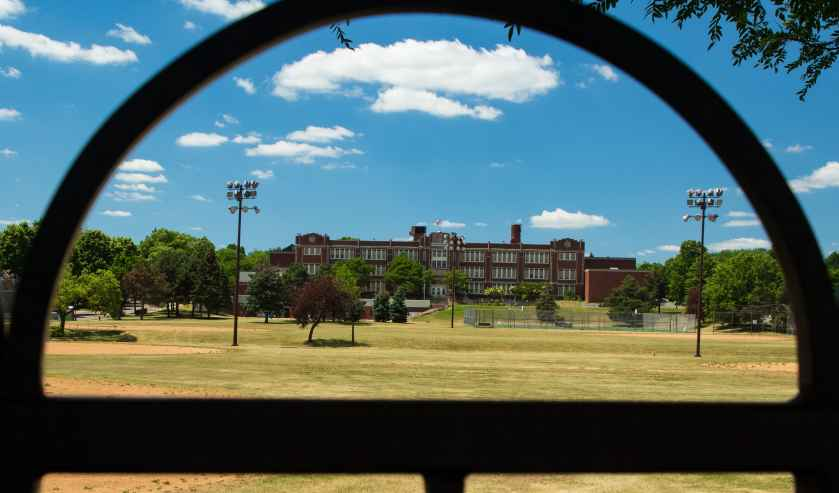 The front (Marion Street side) of Paul & Sheila Wellstone Elementary, built in 1926 as Washington High School. The school is framed through a fence on Rice Street.