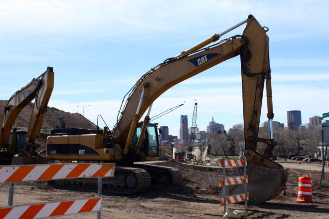 Several Downtown buildings are framed by the boom of a Caterpillar excavator. Before construction began to widen I-35E, this was the corner of Pennsylvania Avenue and L'Orient Street.