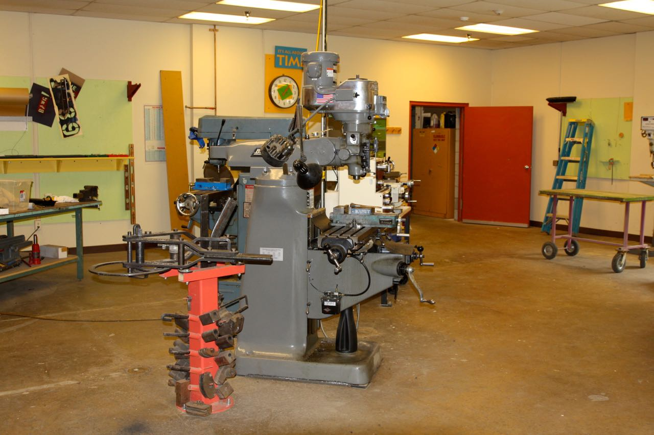 The metal shop includes an industrial drill press.