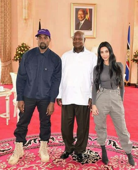 In front of a photo of Ugandan President Yoweri Museveni that Museveni has on display, he poses with American celebrities Kanye West and Kim Kardashian. (Photo courtesy of Twitter)