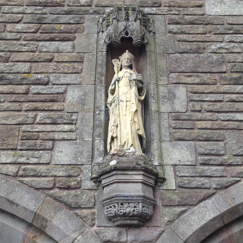 Statue av St. Hilda i det tidligere St. Hilda's Priory i Sneaton Castle i Whitby. Hun bærer abbedissestaven i sin høyre hånd som tegn på religiøs autoritet, og sin klosterkirke i venstre hånd