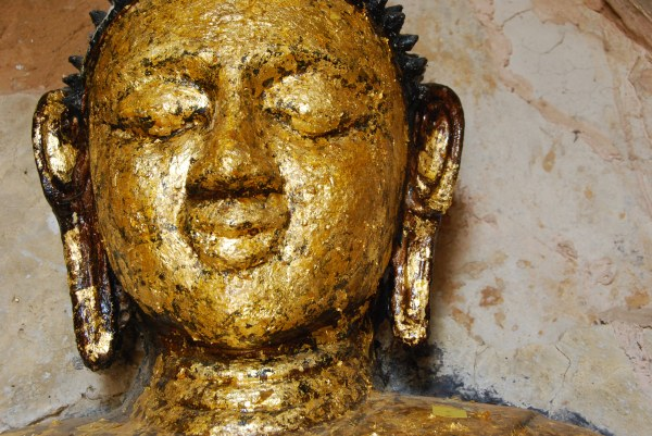 Close-up of a buddha statue with gold leaf applique 2