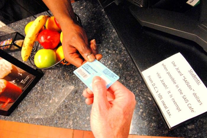 A SAIS student uses the dining dollars on his JHU ID to make a purchase at the Nitze cafe. (SARAH RASHID)
