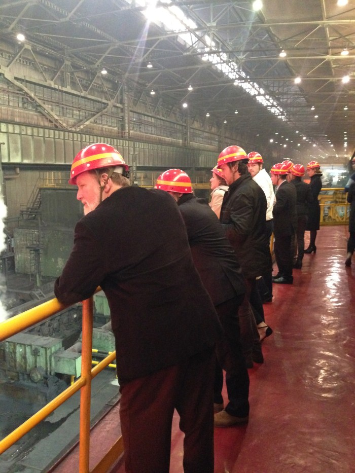 Professor Bruce Parrott (Russian/Eurasian studies, trip leader) and members of the group look on a steel plates are produced at Baosteel in Shanghai. (Photo credit: Sam Rizzo)