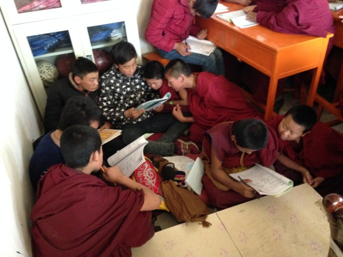 Fitting eighty students into a classroom meant not everyone had a seat. Here some young monks work on an English grammar problem with their peers. (Photo: Chase Stewart)