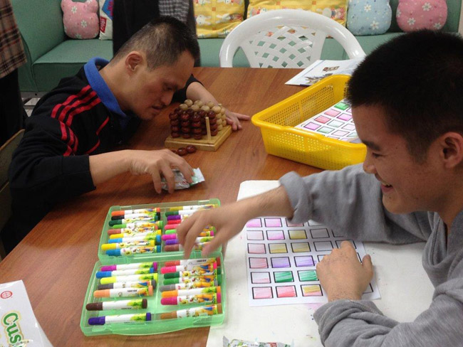 Volunteer playing with disadvantaged resident