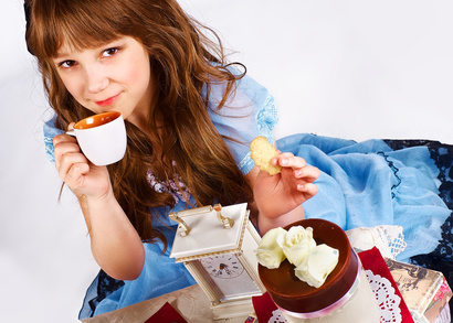 Little girl in a blue dress on the floor drinking tea and eating cookies