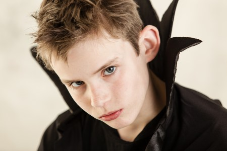 Single cute little boy with serious expression dressed in black vampire cloak over white background