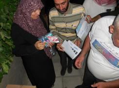 A woman taking the hygiene kits for her children - they contain a tooth brush, tooth paste, soap, comb, and a few small toys