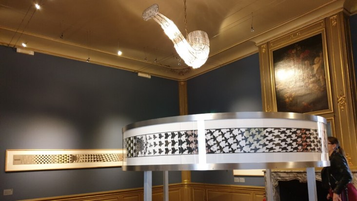 één van de zalen van Escher in het paleis met werk van Escher en een kroonluchter in de vorm van een pijp
