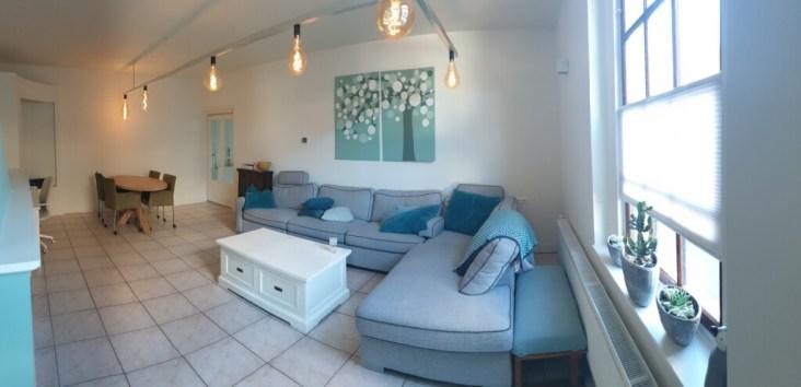 woonkamer met eethoek, grote hoekbank en enorme lamp van een aluminium frame
