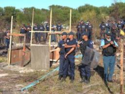 Dozens of police line up on a vacant plot in Khayelitsha taken over by land invaders in a tense stand-off that eventually saw the squatters evicted. File picture: Cindy Waxa