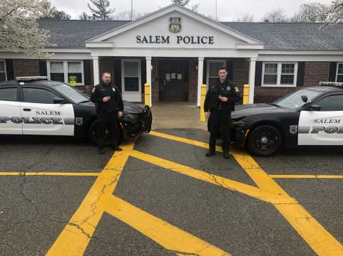 Officer Adam Pearson, left, and Officer Max Greeley hold up challenge coins they were given by the Salem Fire Department last week. (Courtesy Photo Salem Police Department)