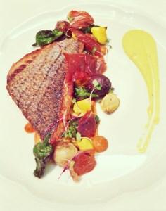 Striped Sea Bass with Romesco Sauce, Summer Squash, Padron Peppers, Baby Potatoes, Serrano Ham Chips, and Lemon Aioli.