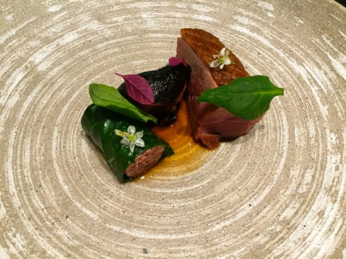 Grilled Duck with Collard Green wrapped Homemade Duck Sausage and Roasted Quince.