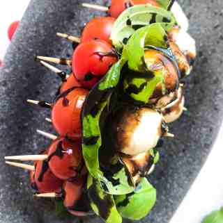 Caprese Salad Skewers on a plate with balsamic glaze.