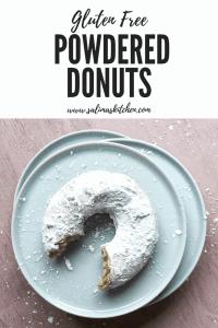 A gluten free powdered donut with a bite taken.