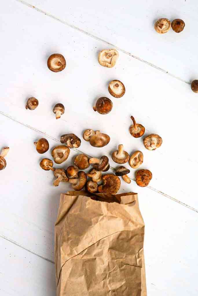 A bag of shiitake mushrooms on a white table.