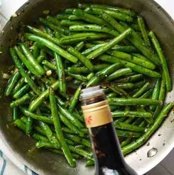 A glug of balsamic vinegar going into a pan of green beans.
