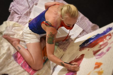 artist Sally Brown wearing a red mask and painting a canvas