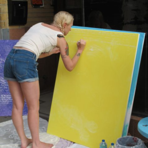 artist Sally Brown drawing on yellow canvas