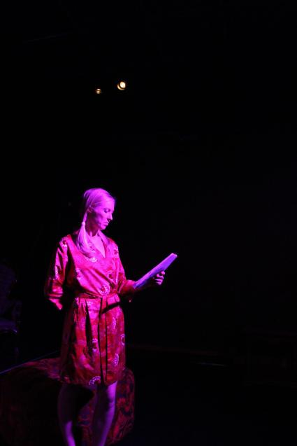 artist Sally Brown speaking on stage in a red dress