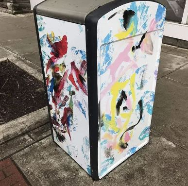 a white trash can covered in multi-colored, abstract paintings of women